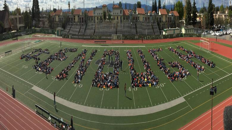 %22At+Granada+Hills+Charter+High+School+in+Los+Angeles%2C+students+lay+down+on+a+football+field+to+spell+out+the+walkout%27s+rallying+cry%3A+%22Enough.%22%22